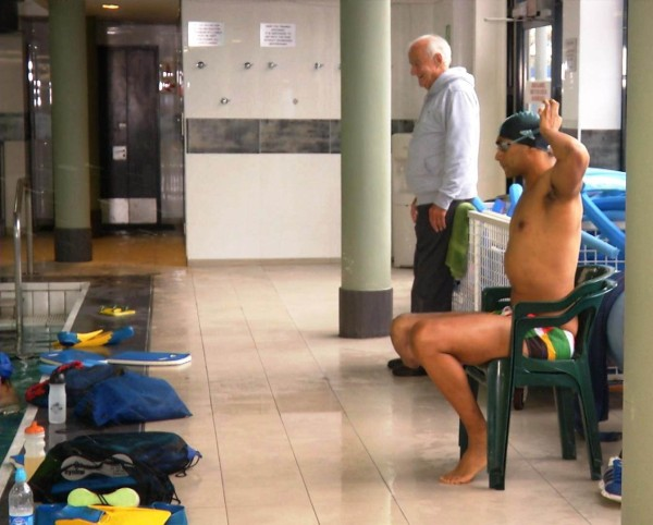 Achmat Hassiem sits by the side of the pool at the Sport Science Institute in Cape Town, South Africa.